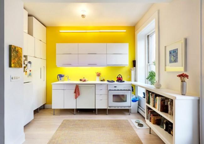 Одна акцентная желтая стена, яркость которой дополнительно подчеркнута лампой дневного света, как фон для белой модульной кухни. Это обстановка для молодых людей, жизнерадостных и легких на подъем