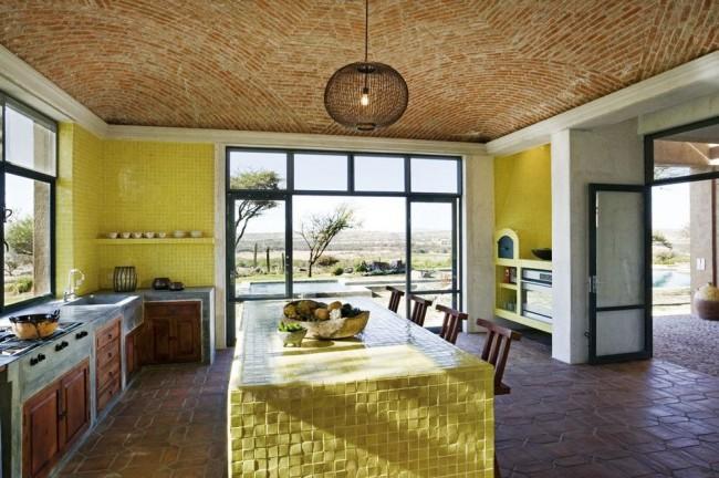 Сочетание желтого цвета в мозаичной плитке с цветом глины, терракота и дерева в фасадах мебели на большой кухне в средиземноморском стиле