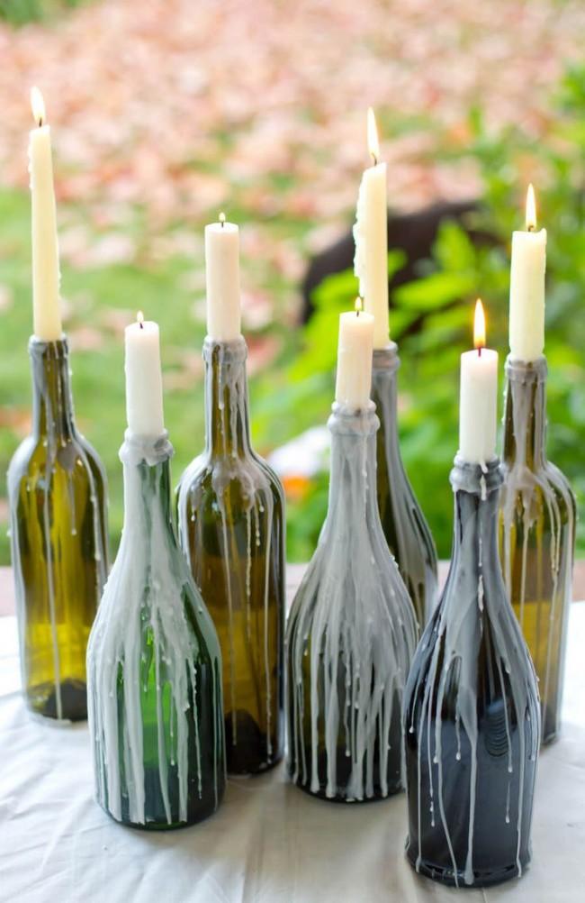 Старые бутылки можно использовать как подсвечник, который сам себя декорирует плавленым парафином