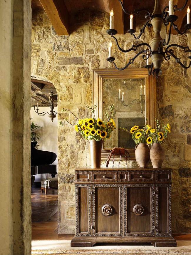 Каменная стена и открытые балки в прихожей, оформленной в стиле средневековой Франции