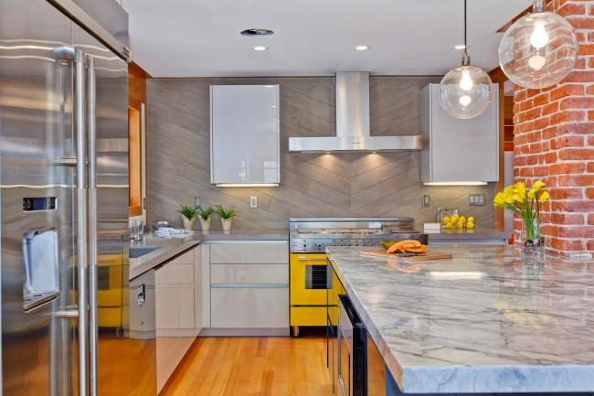 Вытяжка с дополнительной подсветкой на яркой кухне-студии, с кирпичной кладкой на одной из стен, и массивной мраморной столешницей