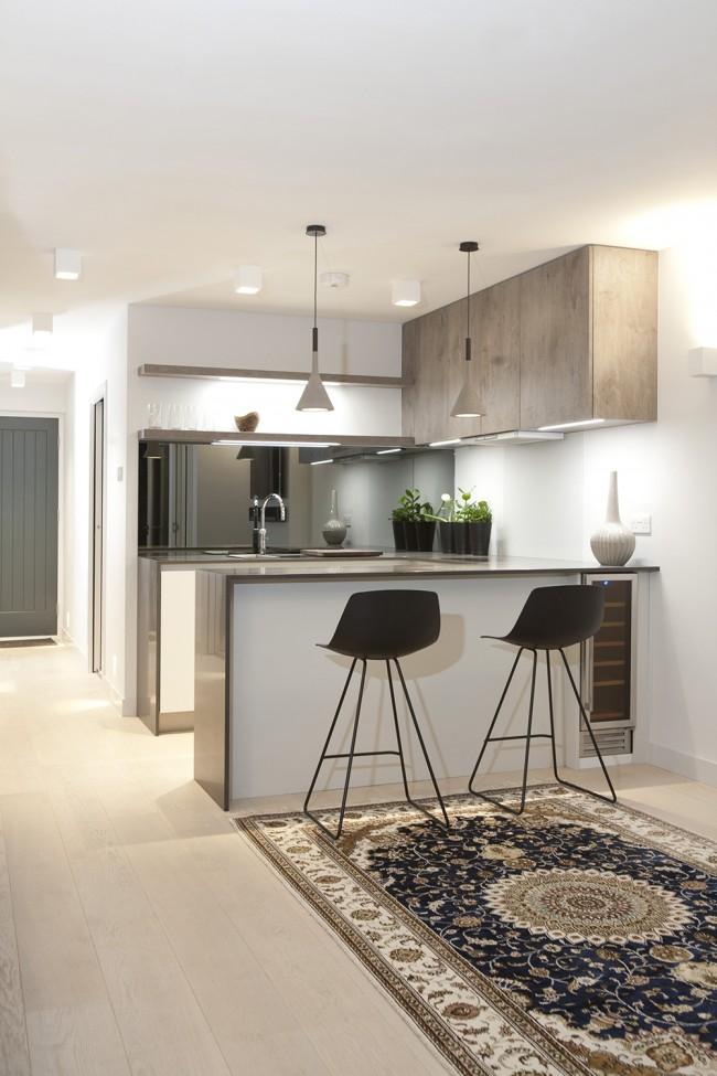 Дополнительная подсветка рабочих зон, а также барной стойки подчеркнет дизайн кухни-студии в светлых тонах и увеличит полезное пространство