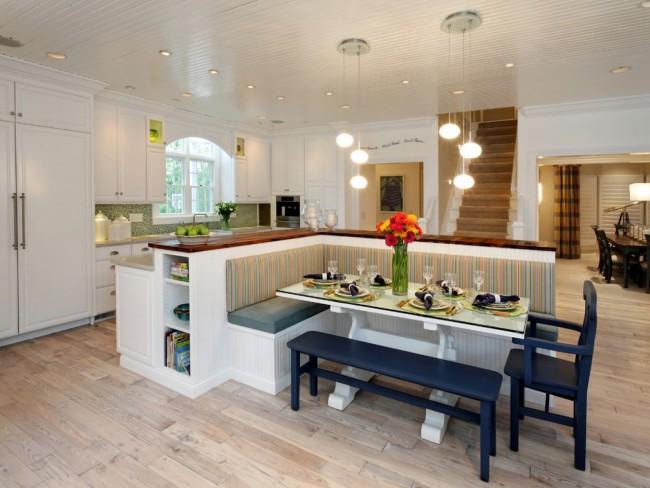 Просторная кухня-студия в светлых тонах с акцентами из натурального дерева и синими штрихами в мебели обеденной зоны