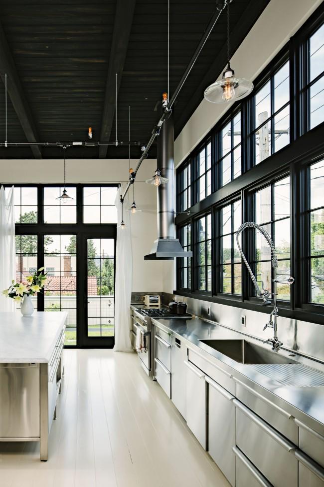 Большая современная кухня в черно-белых тонах в частном доме, с большими окнами, которые обеспечивают максимальное естественное освещение в дневное время суток