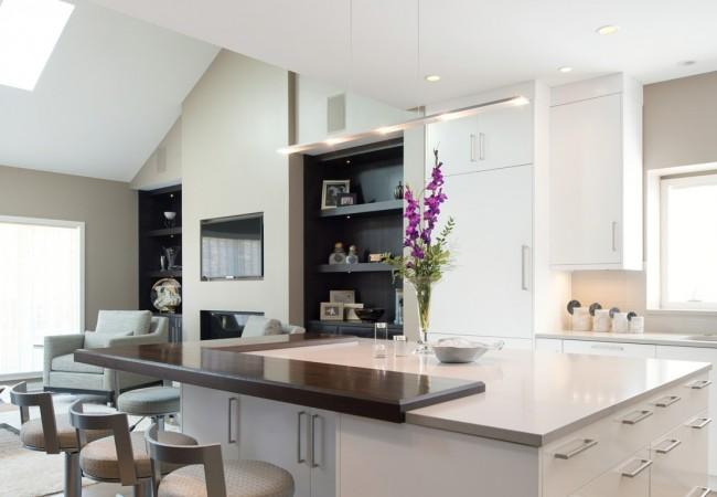 Светлые тона и большое количество естественного освещения визуально увеличивают комнату, а яркие акценты на деревянных элементах дополняют интерьер кухни-студии