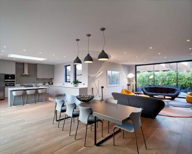 Большой обеденный стол, расположенный между кухней и гостиной