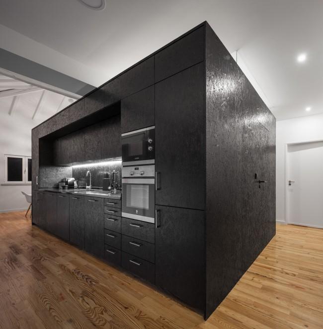 Кухонно-санитарный блок внутри лофта со стенами из плит OSB, выкрашенными в черный цвет и вскрытыми лаком