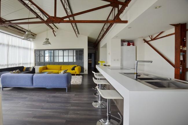 Ржавые конструкции усиленного потолка и комбинированная гостиная и кухня-столовая площадью 50 кв. м на чердачном помещении старой мастерской