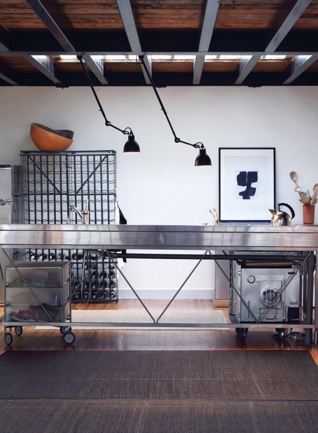 Идея с необычными направленными лампами, крепящимися к потолку, и кухонная мебель из стали и шлифованного алюминия