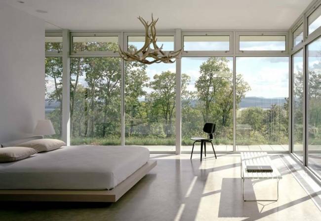 Центр внимания в минималистичной спальне с роскошным видом на посадку деревьев: люстра, имитирующая ветви и сучья