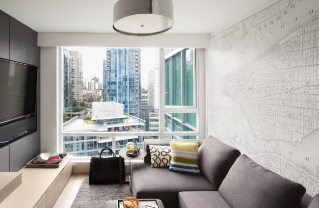 Очень уютная маленькая гостиная в теплых тонах. Большое окно на всю стену визуально увеличивает пространство