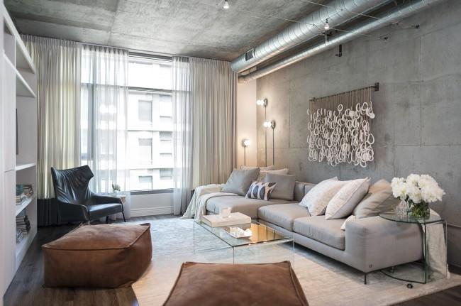 Светлая гостиная с темными штрихами в мебели, визуально увеличивается с помощью большего количества искусственного света, стеклянных поверхностей журнального и прикроватного столиков. Легкие светопрозрачные занавеси днем не препятствуют естественному освещению комнаты