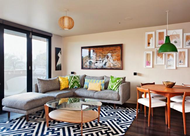 Гостиная объединенная с обеденной зоной легко зонируется с помощью большого ковра в зоне отдыха и отдельного освещения в виде разноплановых люстр