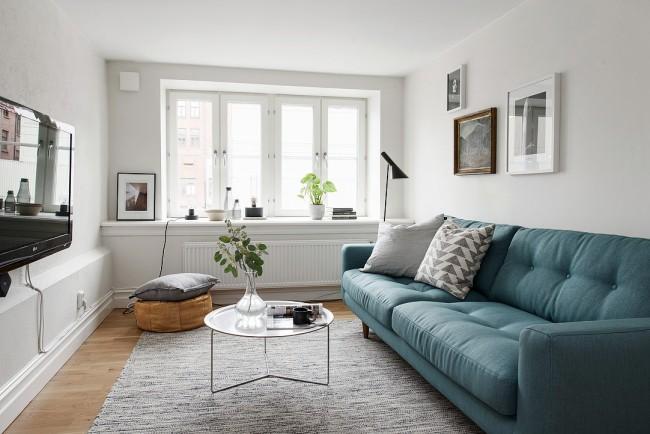 Стеклянный журнальный столик создает легкость в интерьере маленькой гостиной