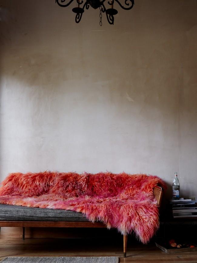 Яркая акцентная накидка из красного искусственного меха в на джинсовом диване обстановке-лофт