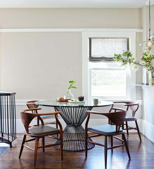 Стеклянный круглый стол и деревянные стулья интересной формы в стиле китч