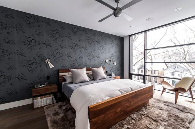 Черные текстильные обои не затемняют, а лишь освежают комнату благодаря панорамным окнам и обильному потоку естественного освещения