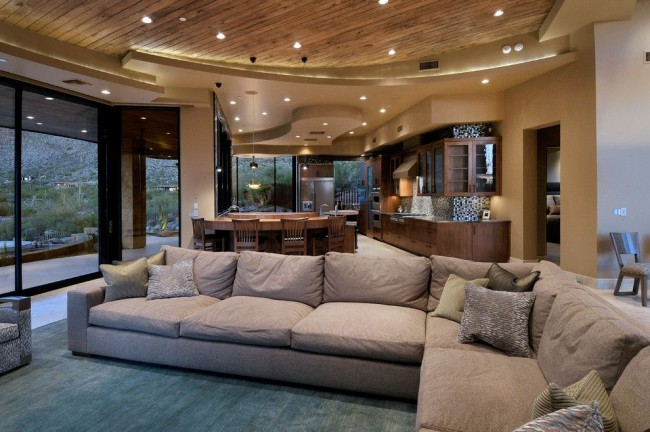 Пример удачного зонирования с помощью точечного освещения и многоуровневого потолка из гипсокартона. Здесь сочетается и кухонная зона, и зона отдыха