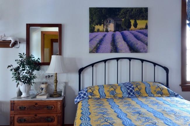 Изображение лавандовых полей на картине в простом интерьере спальни