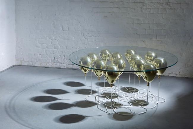 """Креативная работа под названием """"Up!"""" из стекла и металла с """"воздушными"""" шариками, поддерживающими столешницу"""