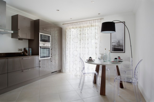 Сдержанное оформление кухни в нейтральных тонах и прозрачная занавесь с геометричным рисунком