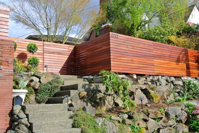 Придомовая территория с ландшафтным дизайном украшена красивым деревянным забором