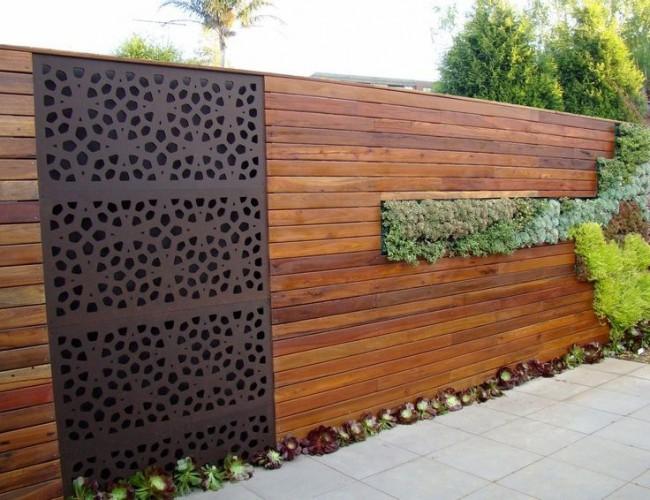 Металлическая узорная вставка в деревянном заборе
