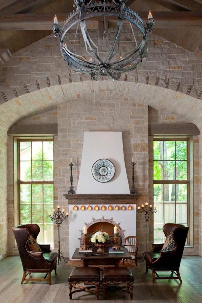 Красивый интерьер гостиной с двумя напольными канделябрами у камина
