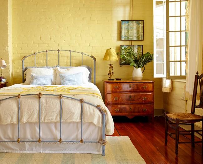 Великолепное сочетание кованной кровати и кирпичной кладки, окрашенной в желтый цвет, в интерьере спальни