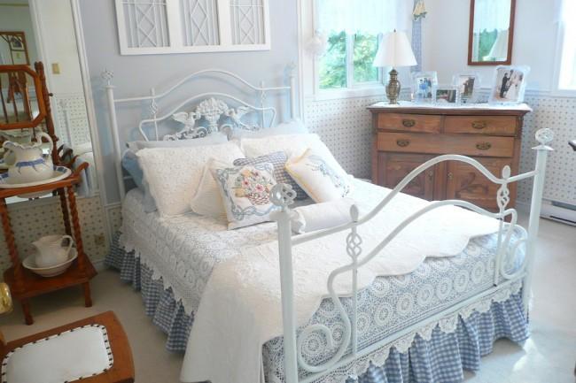 Кровать с элементами ковки, а также текстиль в нежных тонах подчеркнут ваш интерьер в стиле прованс