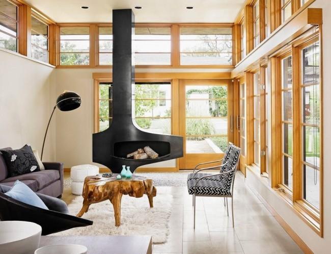 Светло-коричневые деревянные окна и необычный деревянный журнальный столик идеально сочетаются со стилизованным массивным камином черного цвета