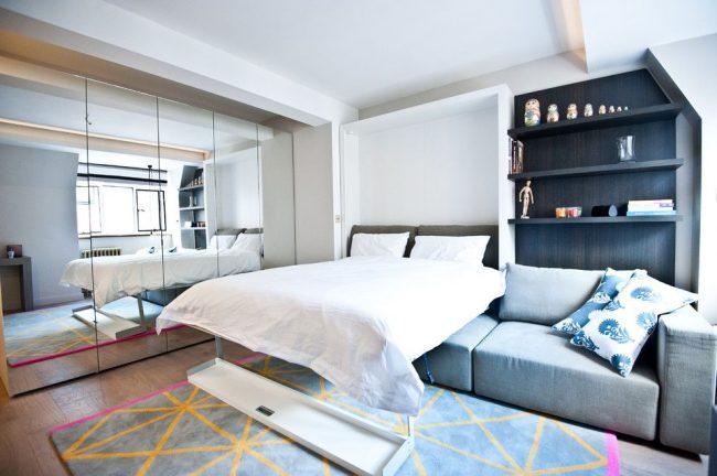 Кровать-трасформер и зеркальный шкаф экономят место, а также визуально увеличивают пространство