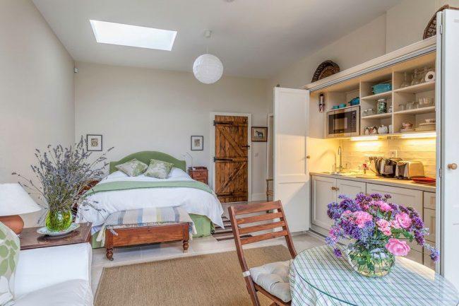 Идеальным решением для небольшой однокомнатной квартиры станут дверцы, скрывающие кухню в шкаф