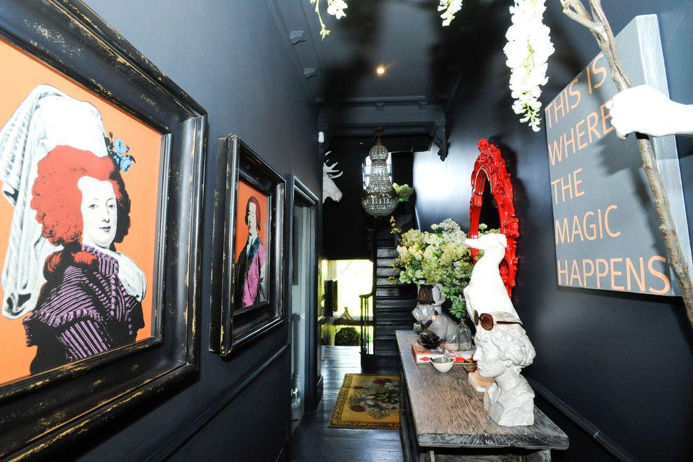 Темный коридор с разноцветными картинами и красным резным зеркалом будет уместен в поп-арт стиле