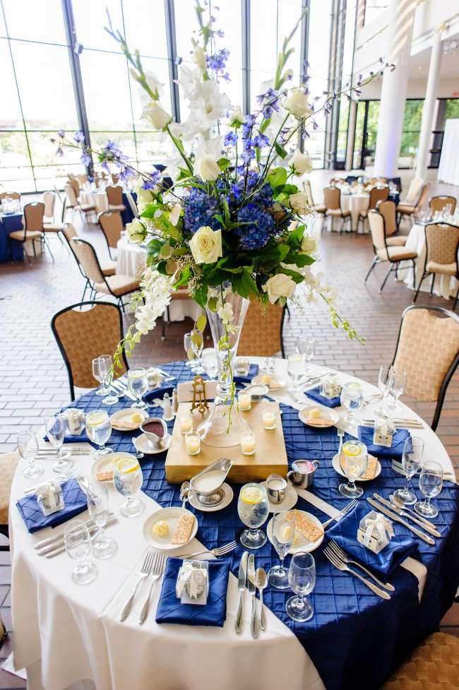 Бело-синяя тема и объемный букет в высокой вазе для оформления столика на 8 персон
