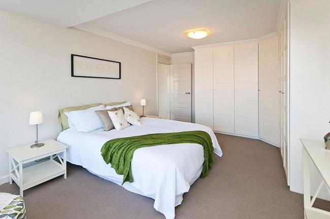 Традиционная спальня с большим белым угловым шкафом