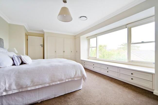 Выдвижные ящики под окном, совмещенные с угловым шкафом в спальне