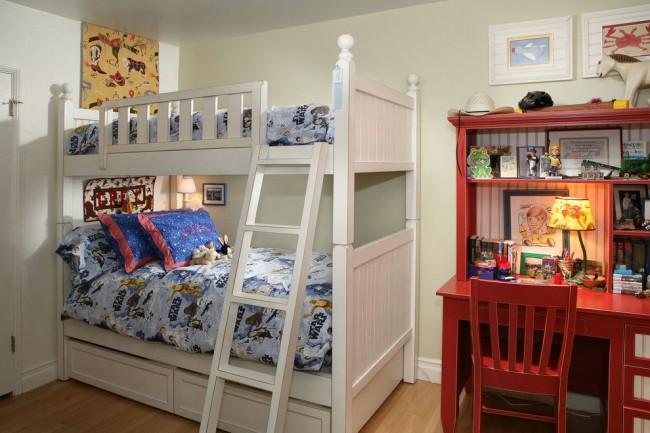 Светлая цветовая гамма детской спальни – отличный фон для заполнения яркими деталями. Рабочая зона кирпичного цвета – яркий тому пример, удачно оттеняющий белую двухъярусную кровать
