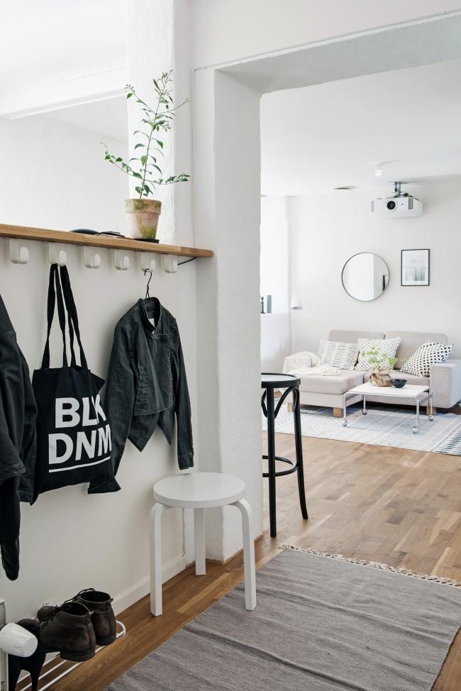 Маленький коридорчик у входа наполненный самым необходимым: подставка для обуви, вешалка для верхней одежды и сумок, а также небольшой стул