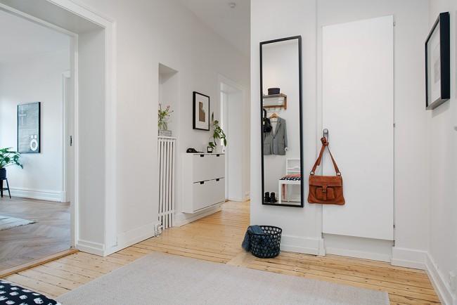 Светлый коридор объединяет комнаты в квартире, не создавая лишних акцентов на себе