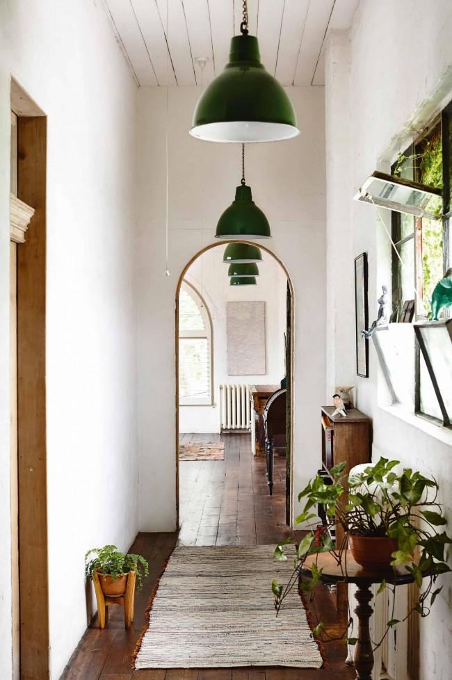 Узкий коридор с акцентом на больших зеленых плафонах и живыми растениями создают уютную атмосферу