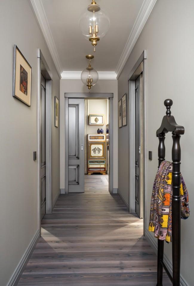 Узкий коридор в нейтральных светлых тонах отлично подойдет для объединения разноплановых комнат в квартире