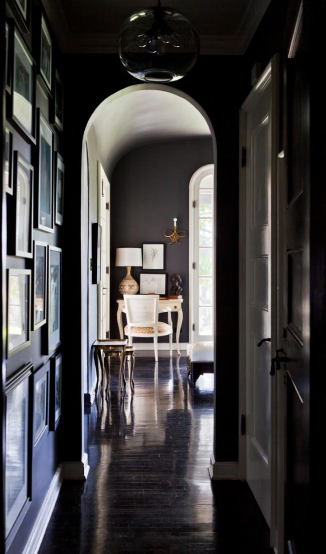 Элегантный темный узкий коридор с большой люстрой и множеством фотографий в рамках, что заполняют абсолютно всю стену