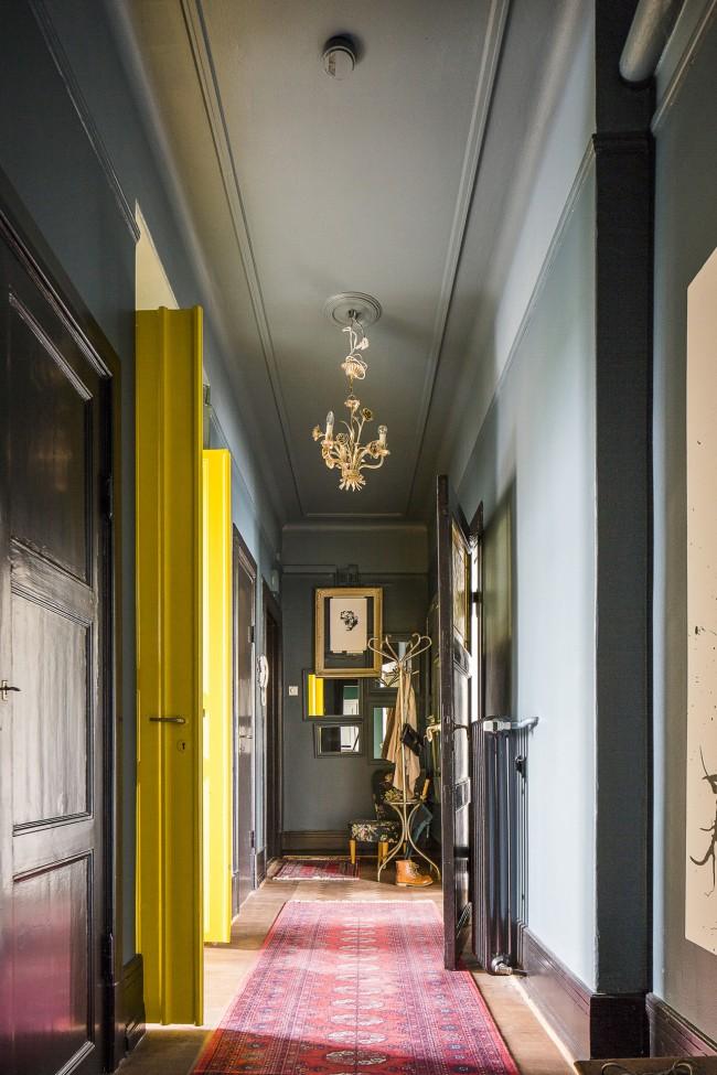 Оригинальный дизайн узкого коридора с акцентами на ярко-желтых дверях и практичном, легкоочищающемся покрытии на стенах