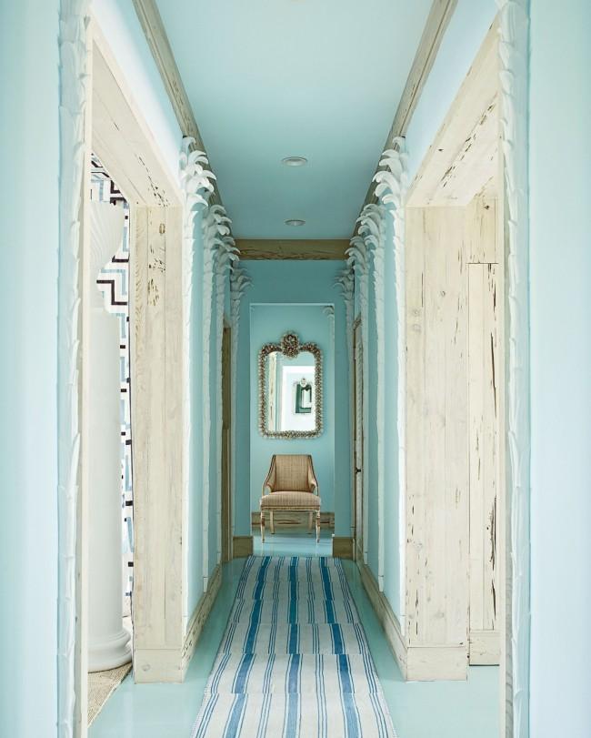 Узкий коридор в очень нежных бирюзовых тонах с точечным освещением и оформлением дверных проемов из натурального дерева
