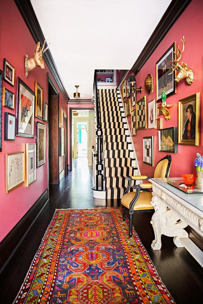 Очень смелое решение: яркие розовые стены и пестрые картины в сочетании с необычным орнаментальным ковром подчеркнут индивидуальность владельца