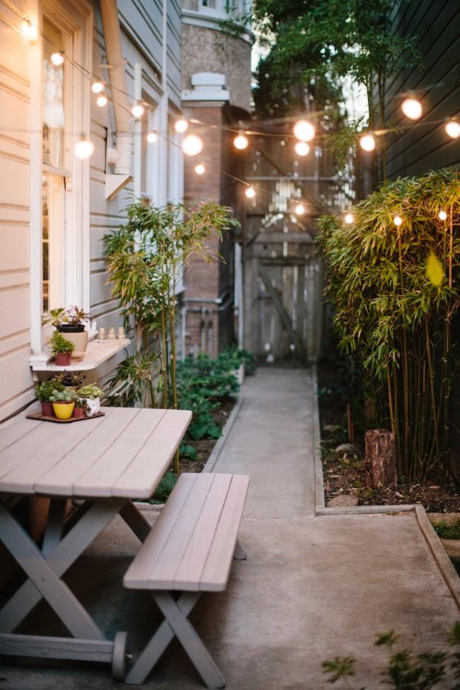 Небольшой узкий столик на компактном заднем дворике