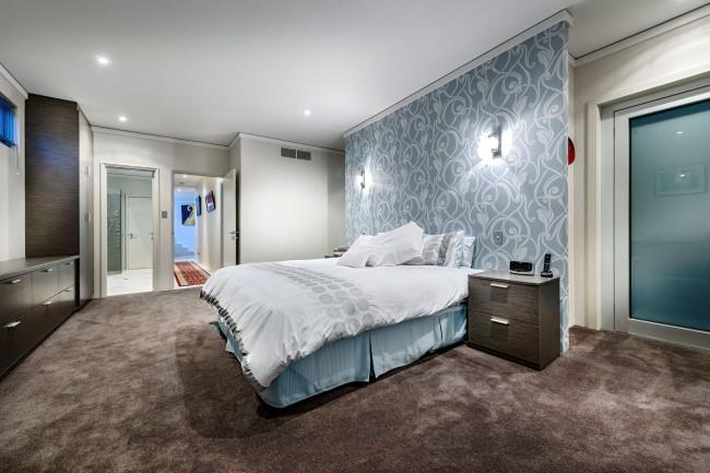 Уютная спальня в преимущественно светлых тонах с темными акцентами. Орнаментальные обои на стене у изголовья кровати акцентируют внимание на зоне отдыха