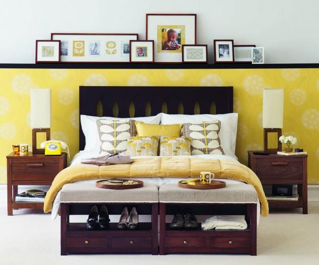 Уютная спальня с желтыми акцентами и оригинальным решением комбинирования: панель разделяющая разноплановые обои также выполняет функцию небольшой полочки для фотографий