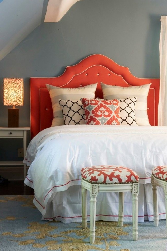 Коралловые акценты: изголовье кровати и принт на пуфах, настольной лампе